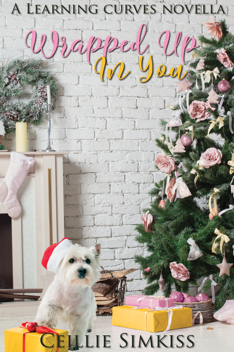 "A scene of a Christmas tree with pale yellow and pink ornaments, flowers, and ribbons. Wrapped pink and yellow presents are under the tree, as well as a small white terrier with a Santa hat with a paw on a present. In the background is a white brick wall and a fireplace with a snow-dusted wreath, tall candles, and a light pink stocking. The title is in a cursive font in pink and yellow, reading ""Wrapped Up In You."" Above the title is the text ""A Learning Curves Novella"" and at the bottom is the author's name, Ceillie Simkiss, both in all caps in a black serif font."